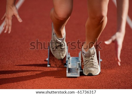 Action packed close-up image of a female athlete leaving the starting blocks for a sprint run on a track