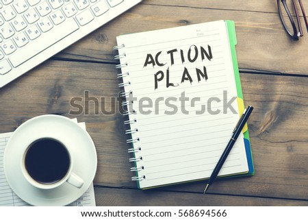 action plan text on notebook with keyboard and coffee on table #568694566