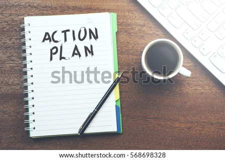 action plan text on notebook with keyboard and coffee on table #568698328
