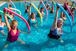 Action portrait of senior aqua gym class. Elderly ladies exercising together with foam noodles in outdoor swimming pool.