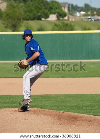 action shot of a high school baseball pitcher winding up to throw the baseball