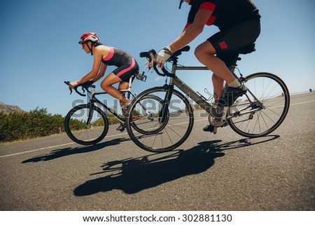 Action shot of a racing cyclists. Cyclist riding bicycles down hill on country road. Practicing for competition.