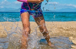 Action shot of an unidentifiable Asian girl having fun, playfully splashing in the water during a summer holiday on an island beach in the Philippines. Legs and waist visible.