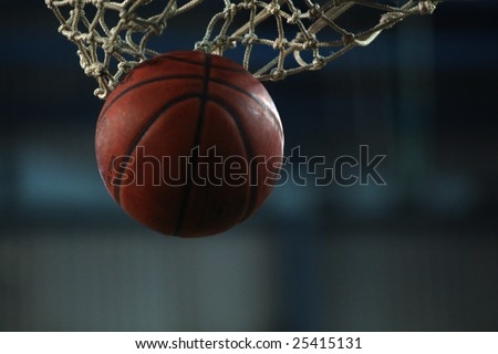 Action shot of basketball going through basketball hoop - stock photo