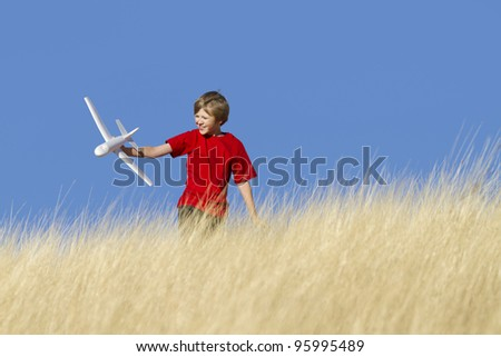 Action shot of boy playing with toy airplane.