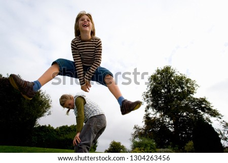 Action shot of children in mid-air playing leapfrog in garden