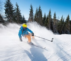 Action shot of professional skier taking selfies photo with a camera on selfie stick while skiing on fresh powder snow in the mountains at the winter resort Bukovel active lifestyle sport concept.