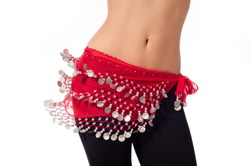 Action shot of the torso of a female belly dancer shaking her hips. She is dressed for rehearsing and practicing belly dance wearing a red coin belt and black leggings. Isolated on white.