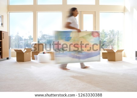 Action shot of woman carrying painting into new home on moving day