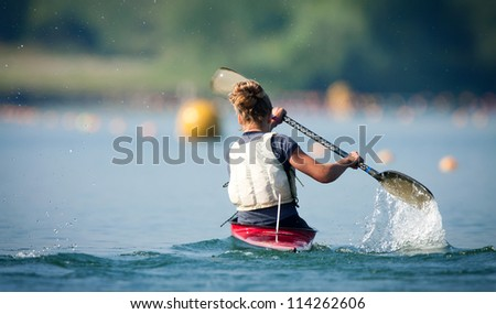 Action Shot of Woman Paddling Kayak in Lake