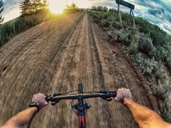 Action shot point of view from a mountain biker cycling down a gravel road towards the sunset.