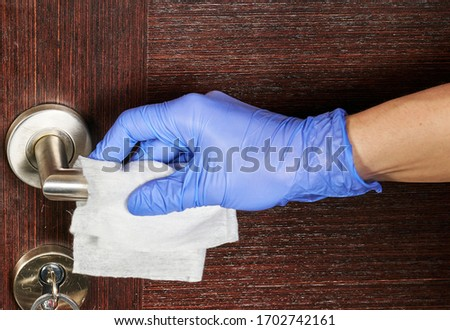 Actions to prevent the spread of coronavirus COVID-19, disinfection of the door handle. Hand in gloves wipes the door handle with a disinfectant Сток-фото ©