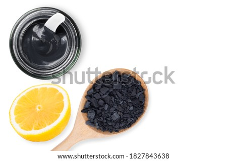 Activated charcoal powder and Clay or charcoal mud cream in glass jar with lemon slice isolated on white background. Top view. Flat lay. Beauty spa, skin care concept. Top view. Flat lay. Сток-фото ©