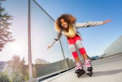 Active African girl rollerblading at skate park