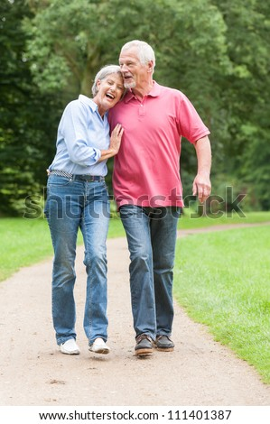 Active and happy senior couple walking in the park - stock photo
