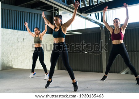 Active and healthy women doing jumping jacks during a HIIT class. Three beautiful and fit women working out at the gym with power training Foto stock ©