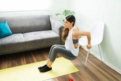 Active and healthy young woman training at home. Beautiful woman in her 20s doing tricep dips with a chair in the living room