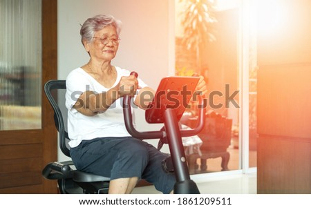 Active Asia senior old woman people training exercise on stationary bike for fit healthy at home gym. Foto stock ©