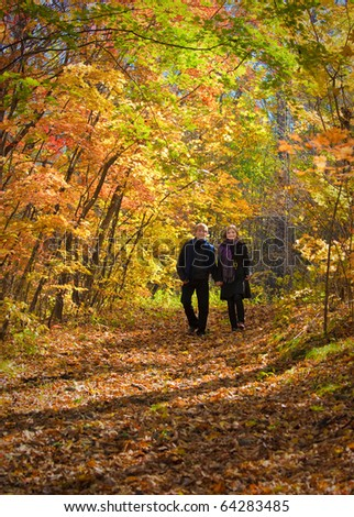 Active beautiful boy and girl in autumn wood - stock photo