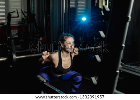 Active beautiful fitness model girl crouches with a barbell on the shoulders in the gym. #1302391957