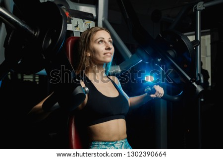 Athletic women training chest on a simulator at gym Images