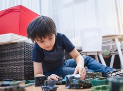 Active boy crawling on floor playing with soldiers and tank toys in playroom, Happy Kid playing wars and peace on his own, Child stay at home relaxing on weekend, Children imagination and development