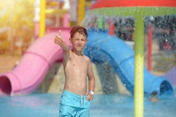 Active Caucasian boy spending his summer holidays in water park, he splashing in pool against colorful plastic slideand showing like gesture.