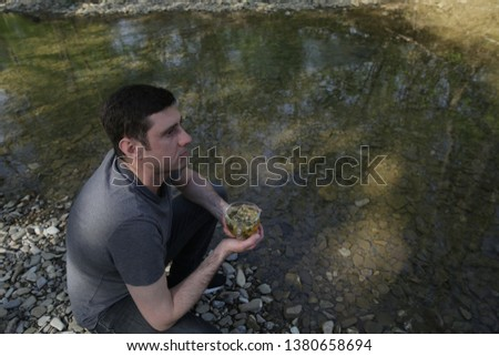 active cheerful man sits by the river in the forest and drinks herbal chamomile tea. The concept of a healthy lifestyle.  #1380658694