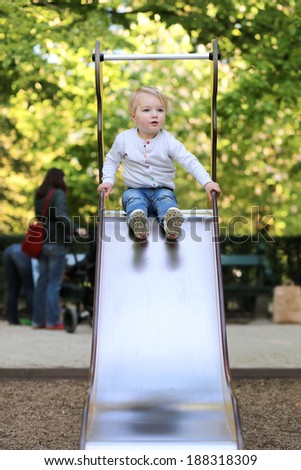 Active child, curly blonde toddler girl having fun in playground on the slide on a sunny summer day