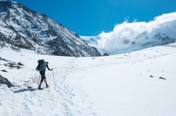 Active climber backpacker man with trekking poles and backpack climbing Mont Blank mount in French Alps mountains during high altitude acclimatization walking.  Extreme active people concept image.
