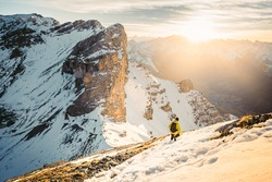 Active climber backpacker man with yellow jacket and backpack climbing in Alps mountains during high altitude acclimatization walking. Extreme active people concept image. Mountain panorama. Sunrise