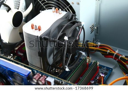 Active cooler for computer processor (cpu), concretely for socket 775. in the background you can see power supply unit and white outtake fan.