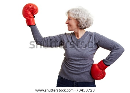 Active elderly woman fighting with red boxing gloves