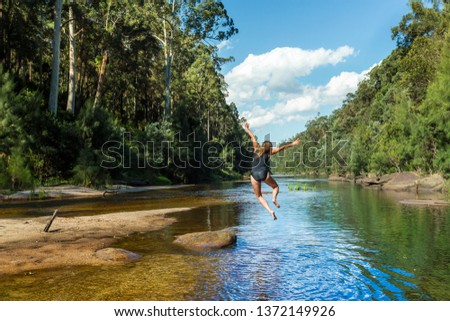 Active exuberant woman jumping into river in remote bushland paradise.  Blue Mountains Australia