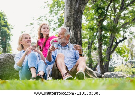 Active family elderly caucasian and child caucasian sitting on lawn relax in weekend holiday lifestyle park outdoor nature background,happy family concept. #1101583883