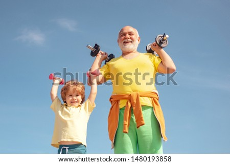Active family enjoy sport and fitness. Funny old senior man and kid boy with dumbbells. Grandfather and child do morning exercise