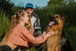 Active Family, fitness couple, Pet Love, Dog Training, best dog breeds for family. Young sports couple walking with two German Shepherd dogs outdoors in summer park