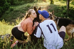 Active Family, fitness couple, Pet Love, Dog Training, best dog breeds for family. Young sports couple walking with two German Shepherd dogs outdoors in summer park.