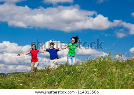 Active family - mother and kids running outdoor - stock photo
