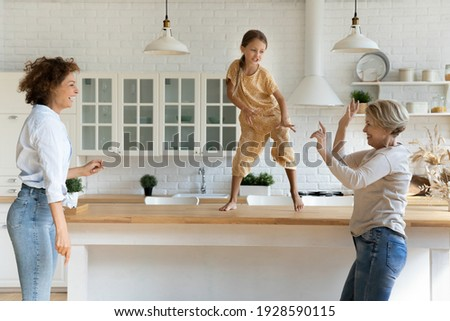 Active family of 3 female generations retired grandma adult mom little daughter grandchild have fun dance at modern kitchen. Energetic dynasty granny mom kid girl jump by music on funny party at home