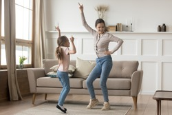Active family young mother dance having fun with little preschool or school age daughter older younger sister listens happy song moving together, leisure activities with kid positive emotions concept