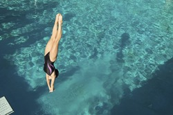 Active female diver diving upside down into the swimming pool