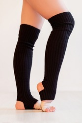 Active footwear. Dance accessories. Female sportswear. Ballet school. Unrecognizable woman in black leg warmers socks training isolated on neutral background.