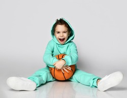 Active frolic kid boy in modern green, mint color sportswear hoodie and pants and white sneakers sits on floor holding basketball ball and with his hood on his head on white background