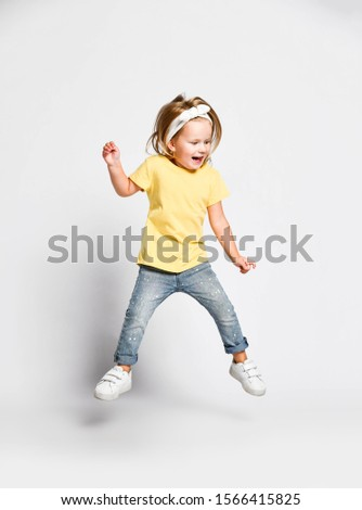 Active gamboling happy screaming kid baby girl blonde in yellow t-shirt, blue jeans and sneakers is jumping high, having fun, flying on white background Stock fotó ©