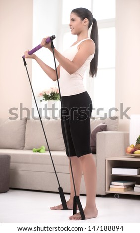 Active girl at home. Side view of confident young women in sports clothing exercising at home