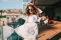 Active girl  in sunglasses is listening to music through headphones on the terrace. She wears a white dress with bare shoulders, red lipstick and hat . She is dancing like crazy