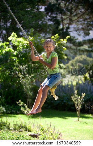 Active girl swinging on garden rope swing having fun at camera