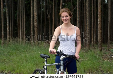 Active girl woman in forest with mountain bike