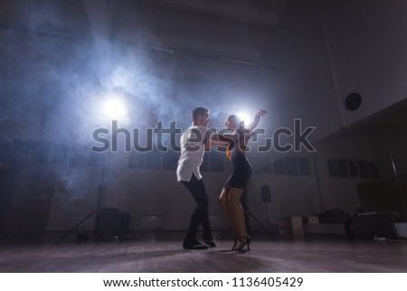 Active happy adults dancing bachata together in dance class #1136405429